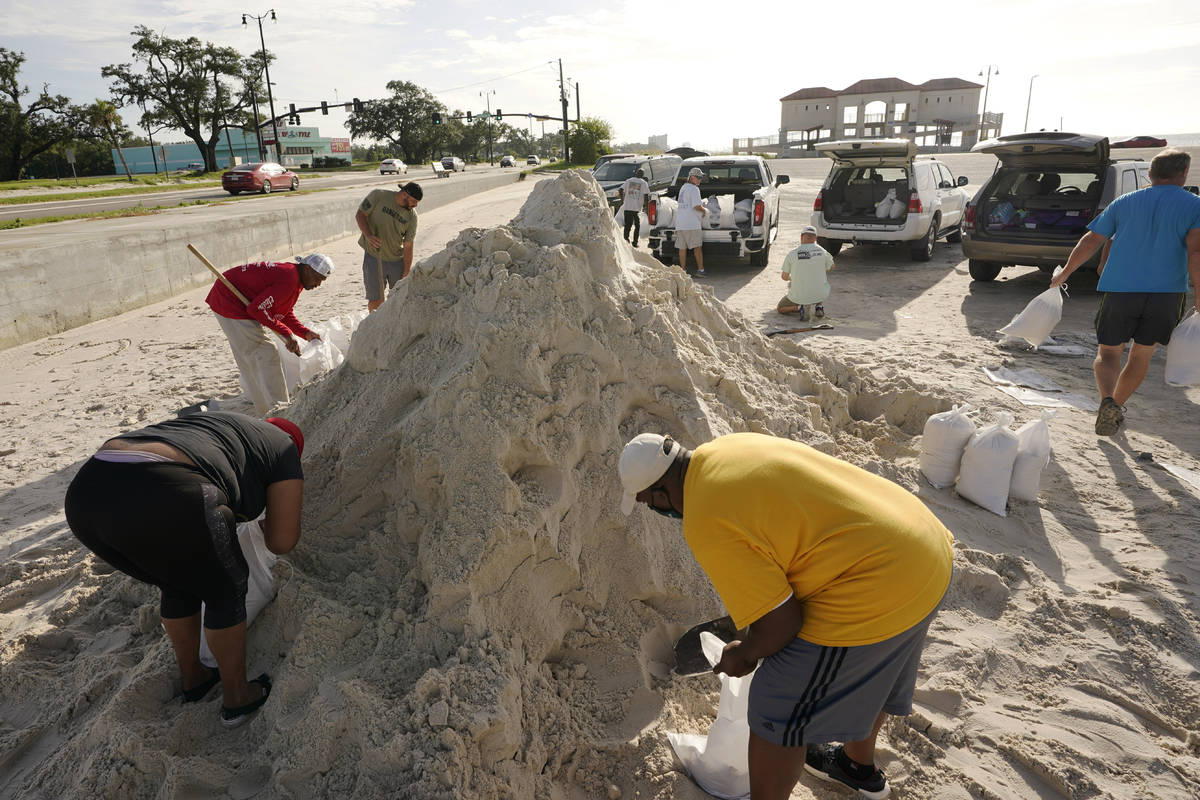 Local residents fill sand bags as they prepare for the expected arrival of Hurricane Ida Saturd ...