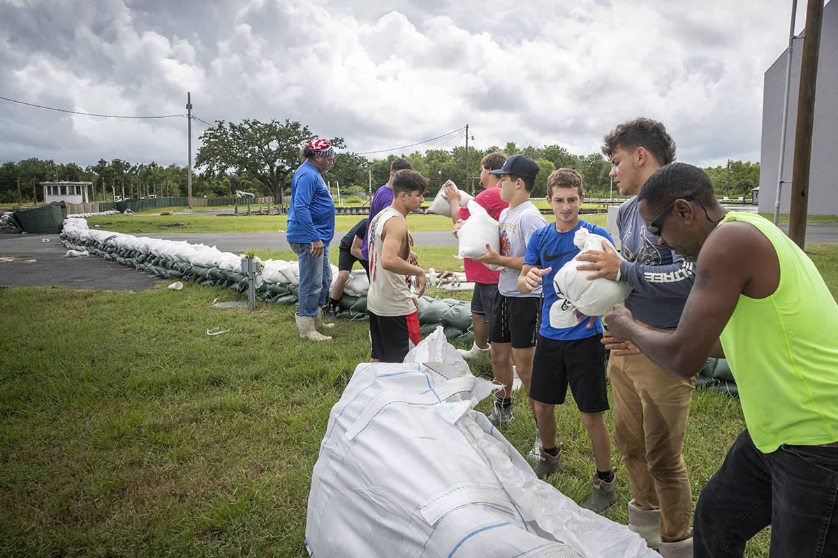 Fisher High School football and basketball players help build a sandbag levee near Tidewater Do ...