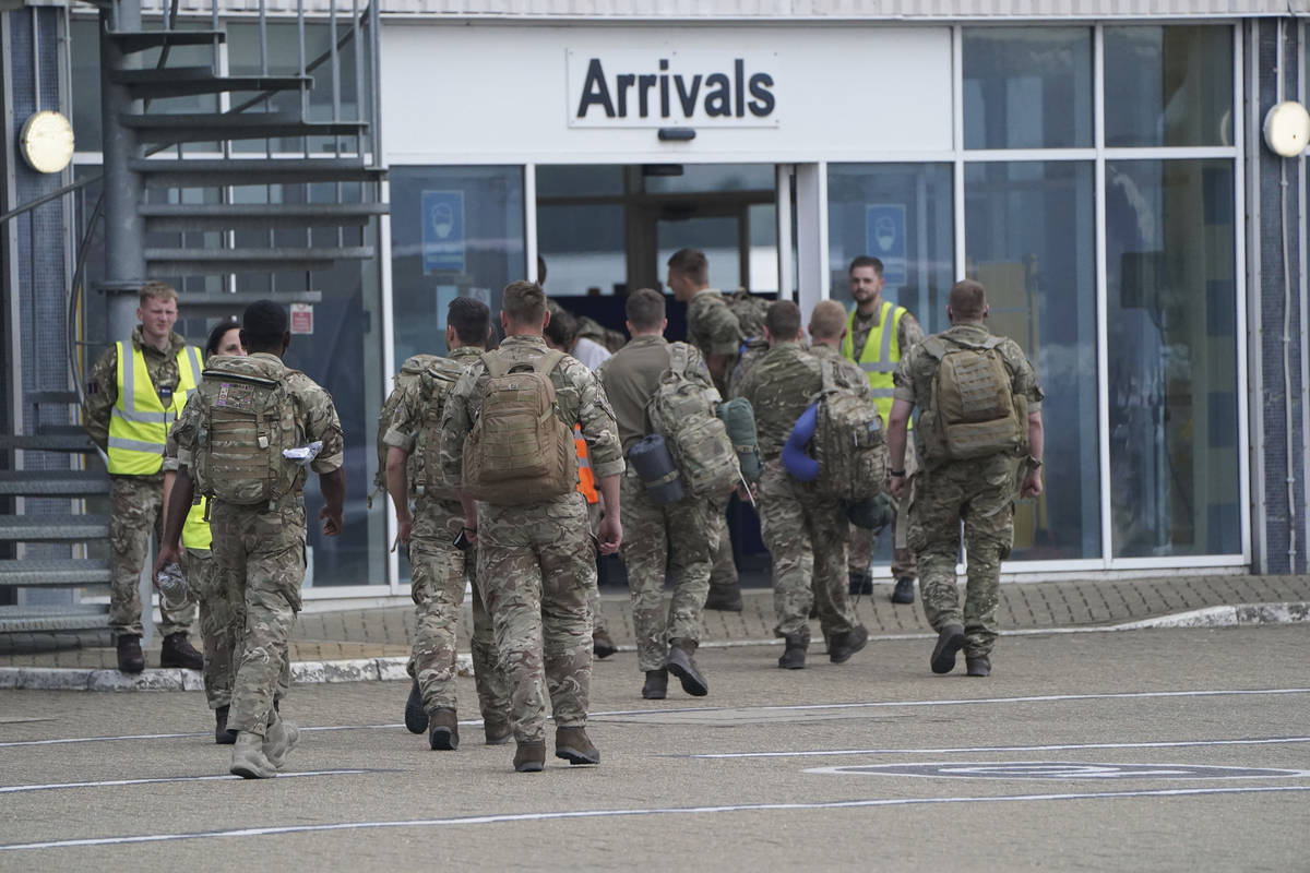 Members of the British armed forces 16 Air Assault Brigade walk to the air terminal after disem ...