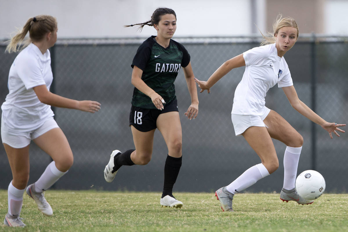 Foothill's Bailey Freeman (15) receives a pass while Green Valley's Brenna Knight (18) runs beh ...