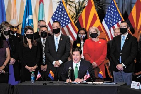 Surrounded by Arizona legislators, Republican Arizona Gov. Doug Ducey speaks at a bill signing ...
