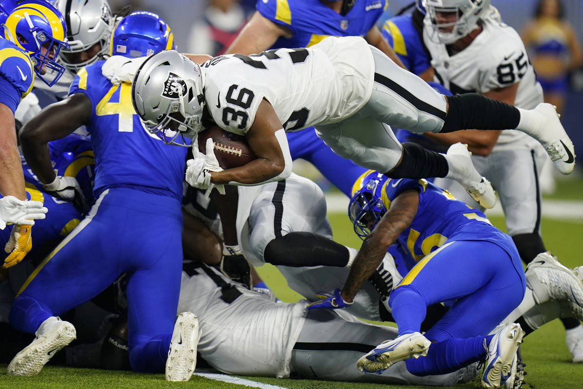 Las Vegas Raiders running back Trey Ragas lunges into the end zone for a rushing touchdown duri ...