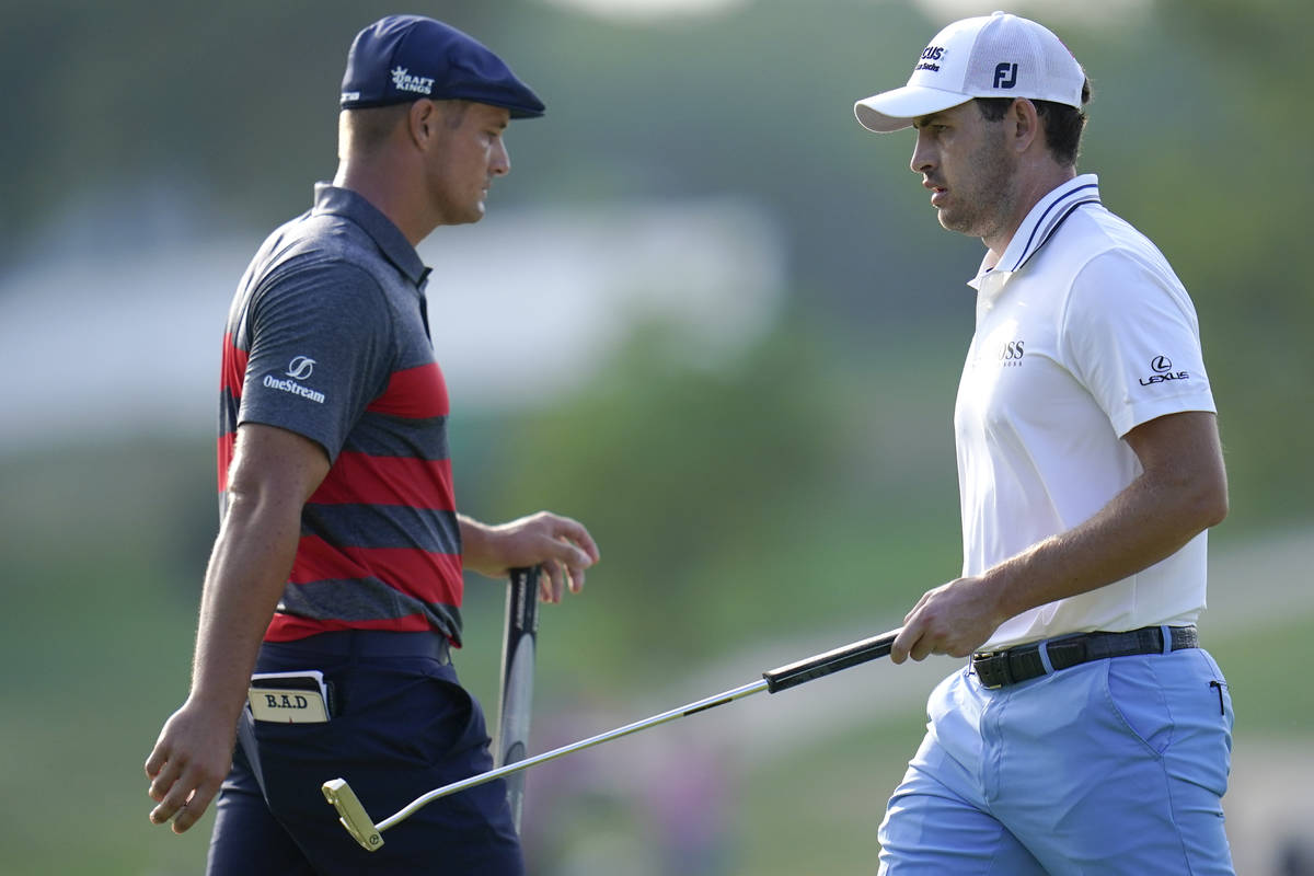 Patrick Cantlay, right, walks by Bryson DeChambeau after he sank his putt on the 17th green dur ...