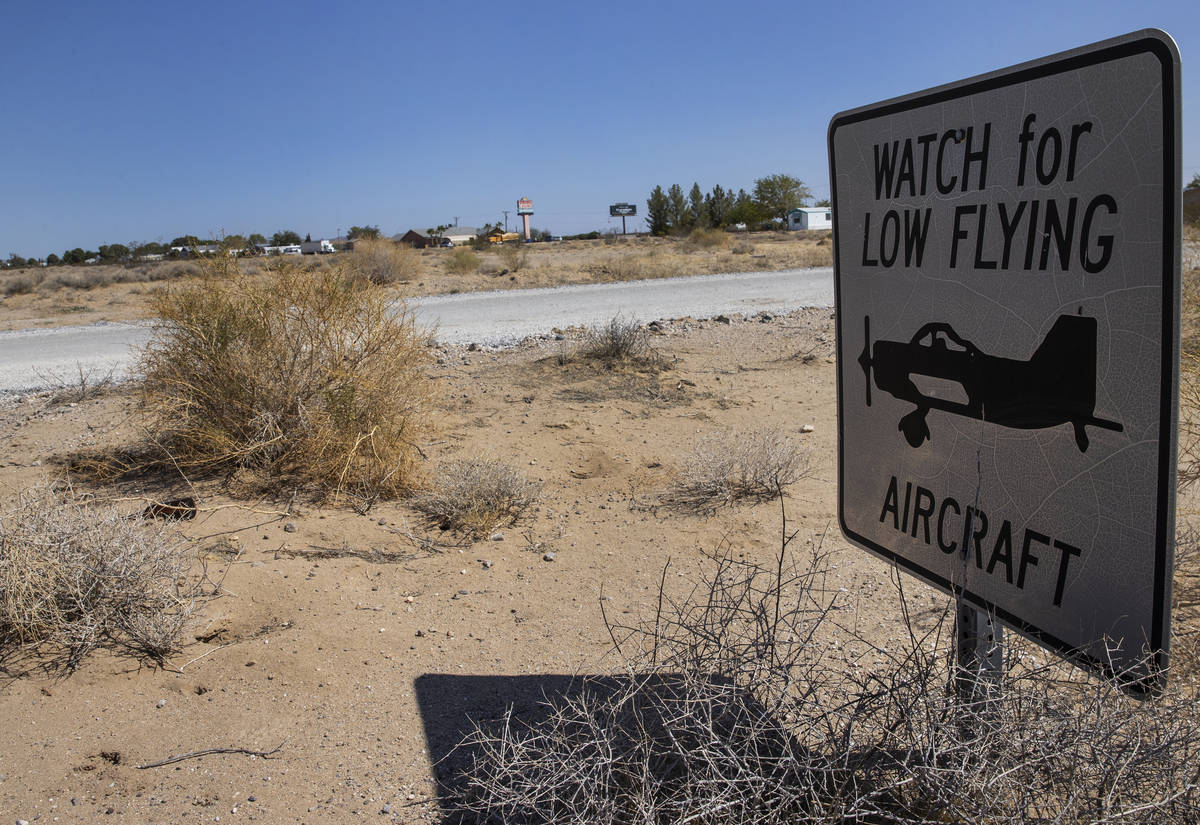 The sign warning residents to watch for low flying aircraft is shown near unpaved airstrip, on ...