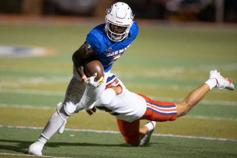 Bishop Gorman's Zachariah Branch (1) breaks a tackle from St. Louis Kona Moore (2) during the t ...