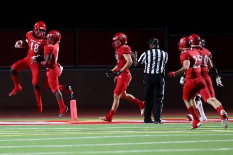 Arbor View's David Washington (18) celebrates a touchdown with Makhai Donaldson (27) during the ...