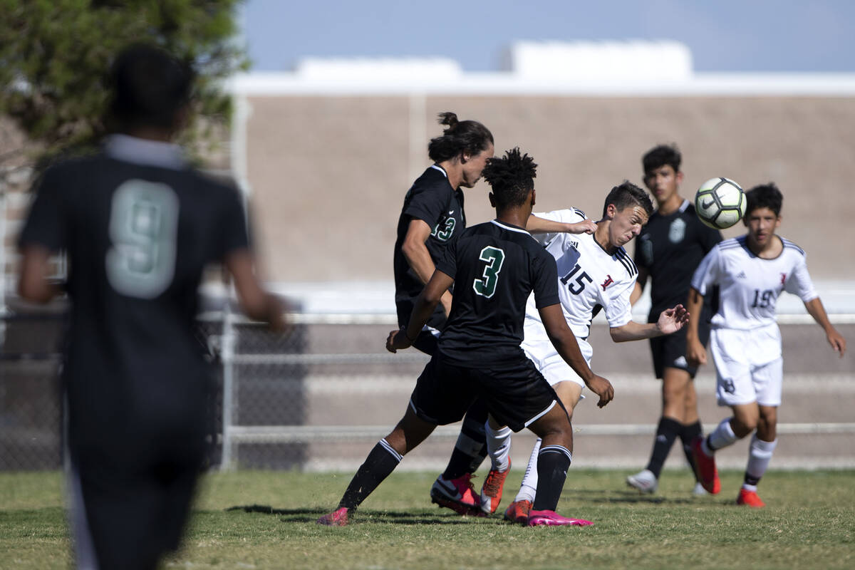Liberty's Anthony Angotti (15) heads the ball surrounded by Palo Verde's Quentin Gomez (13) and ...