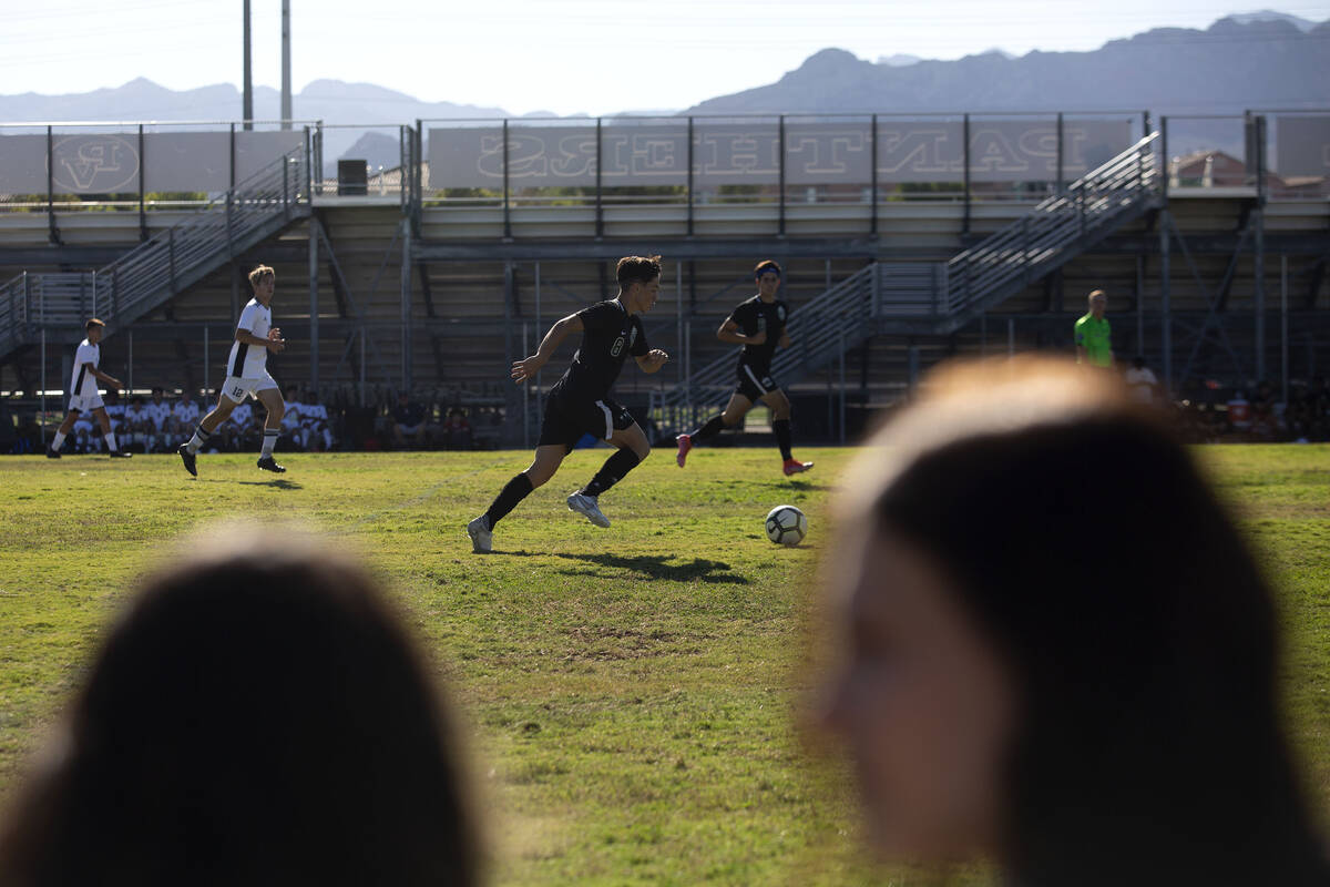 Palo Verde's Elad Cohen (8) makes way down the field while fans chat in the foreground during a ...