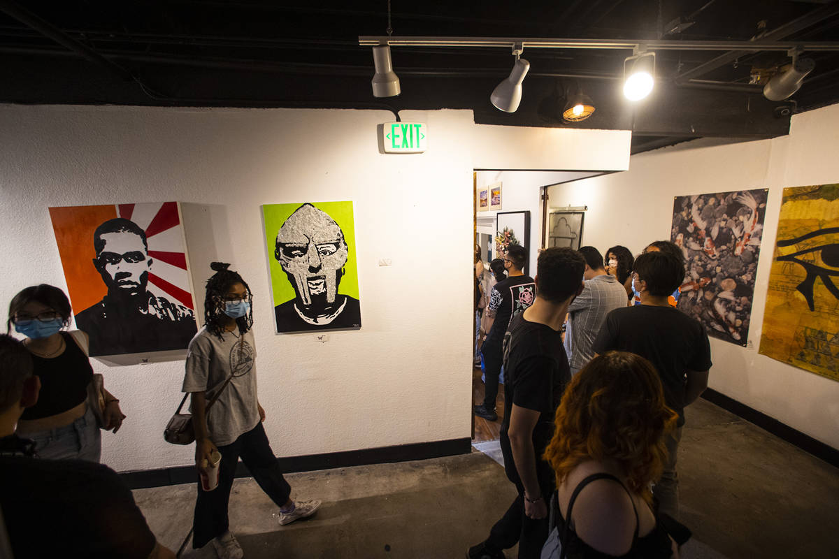 People walk past a portrait of the late rapper MF DOOM by artist Taylor Rene Williams at the Ar ...