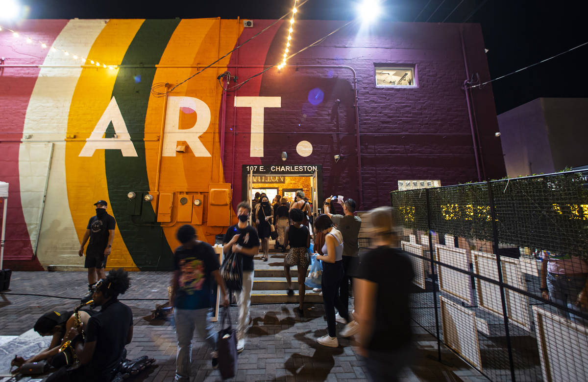 People walk around outside of the Arts Factory during First Friday in the Arts District of down ...