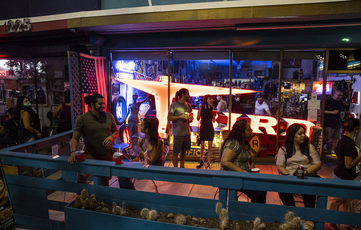 People enjoy drinks and music from a DJ at Vintage Vegas Antiques during First Friday in the Ar ...