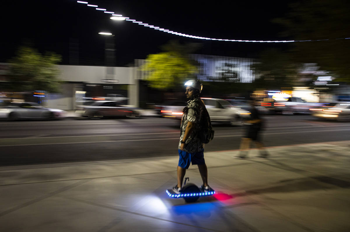 A man passes by on a Onewheel electric skateboard on Main Street during First Friday in the Art ...