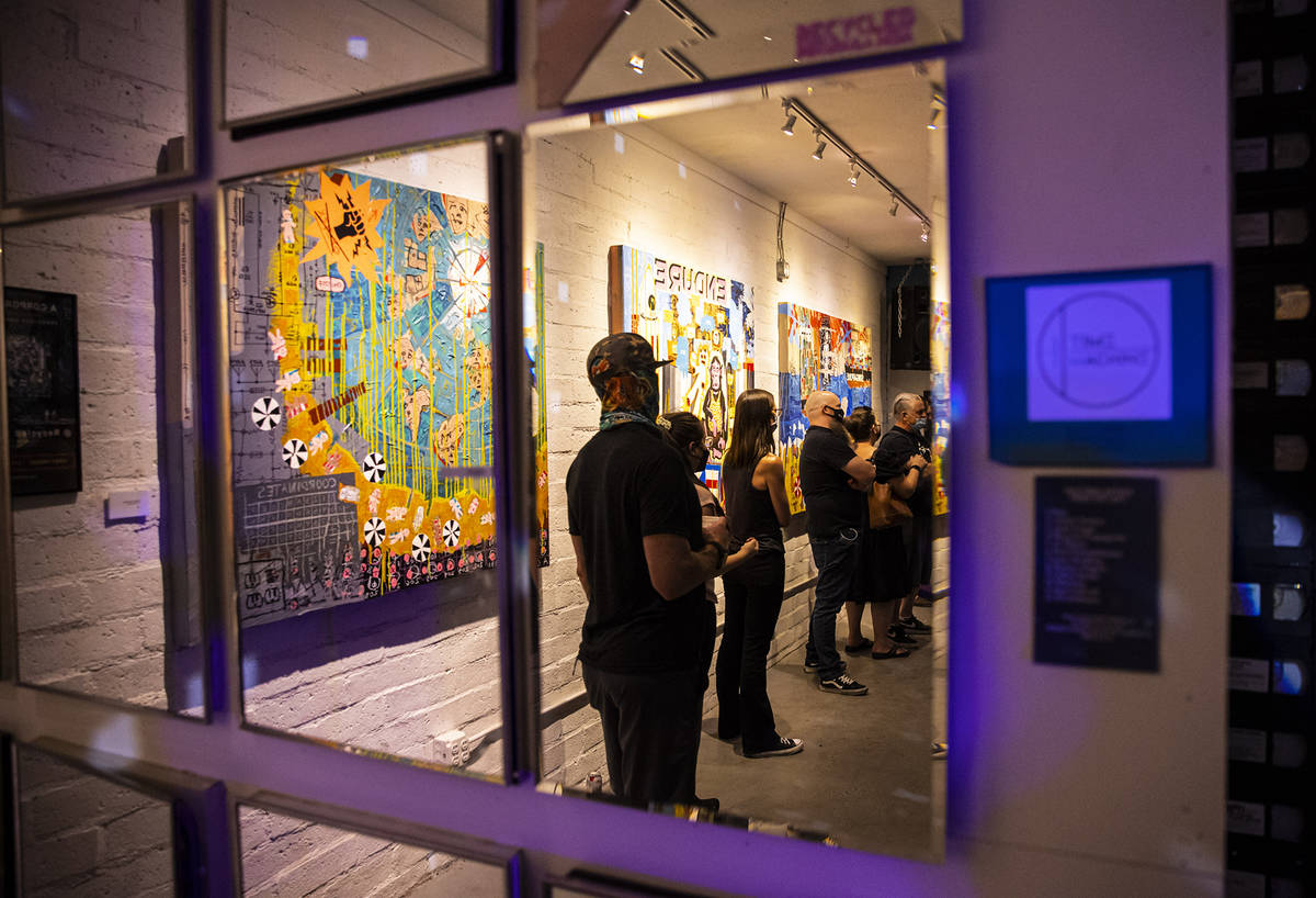 People, reflected in a mirror, watch a performer at Recycled Propaganda during First Friday in ...