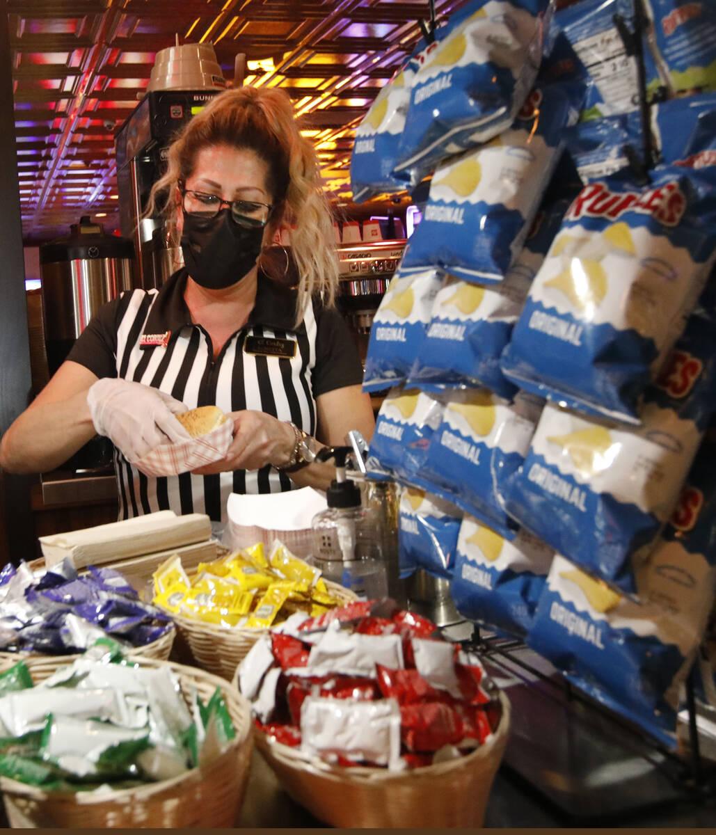 Snack Bar Attendant Loretta Maletto makes a hotdog for a customer at El Cortez in Las Vegas, Sa ...