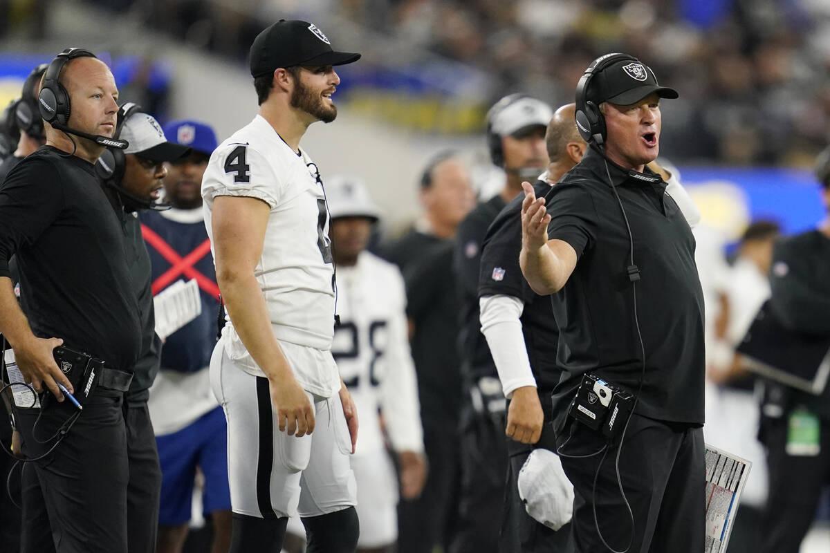 Las Vegas Raiders head coach Jon Gruden, right, argues a call in front of quarterback Derek Car ...
