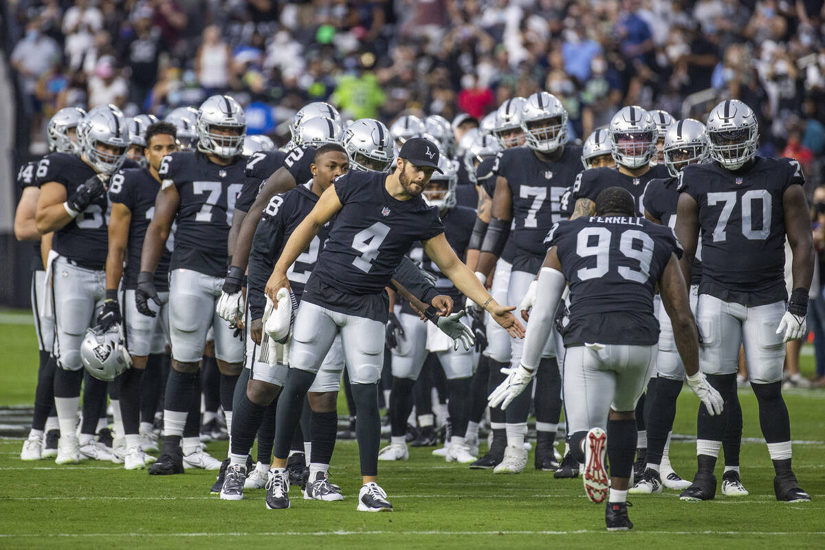 Raiders quarterback Derek Carr (4) and teammates welcome their starters to the field before the ...