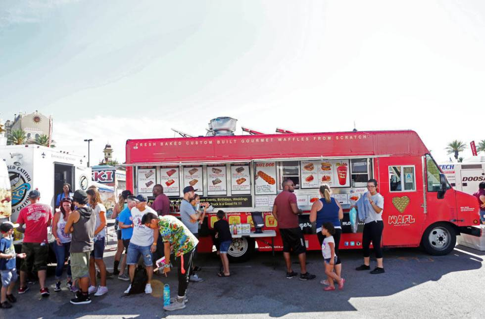 Individuals wait to receive their WAFL Truck waffles during the Great American Foodie Fest ...