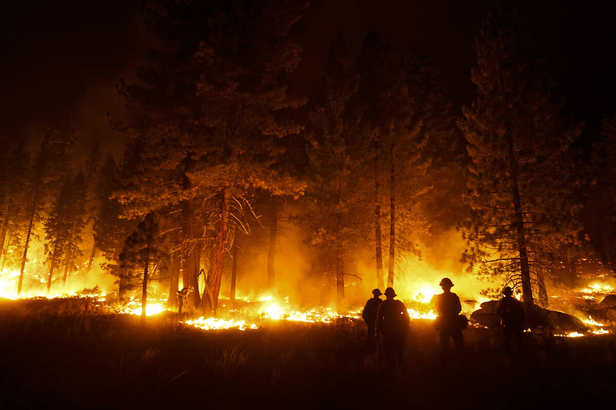 FILE - In this Sept. 1, 2021, file photo, a firefighter lights a backfire to stop the Caldor Fi ...