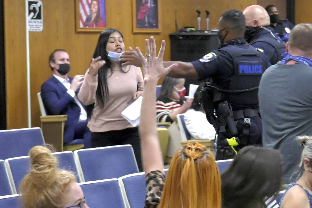 Security personnel approach a woman during Thursday's Clark County School Board meeting. (James ...