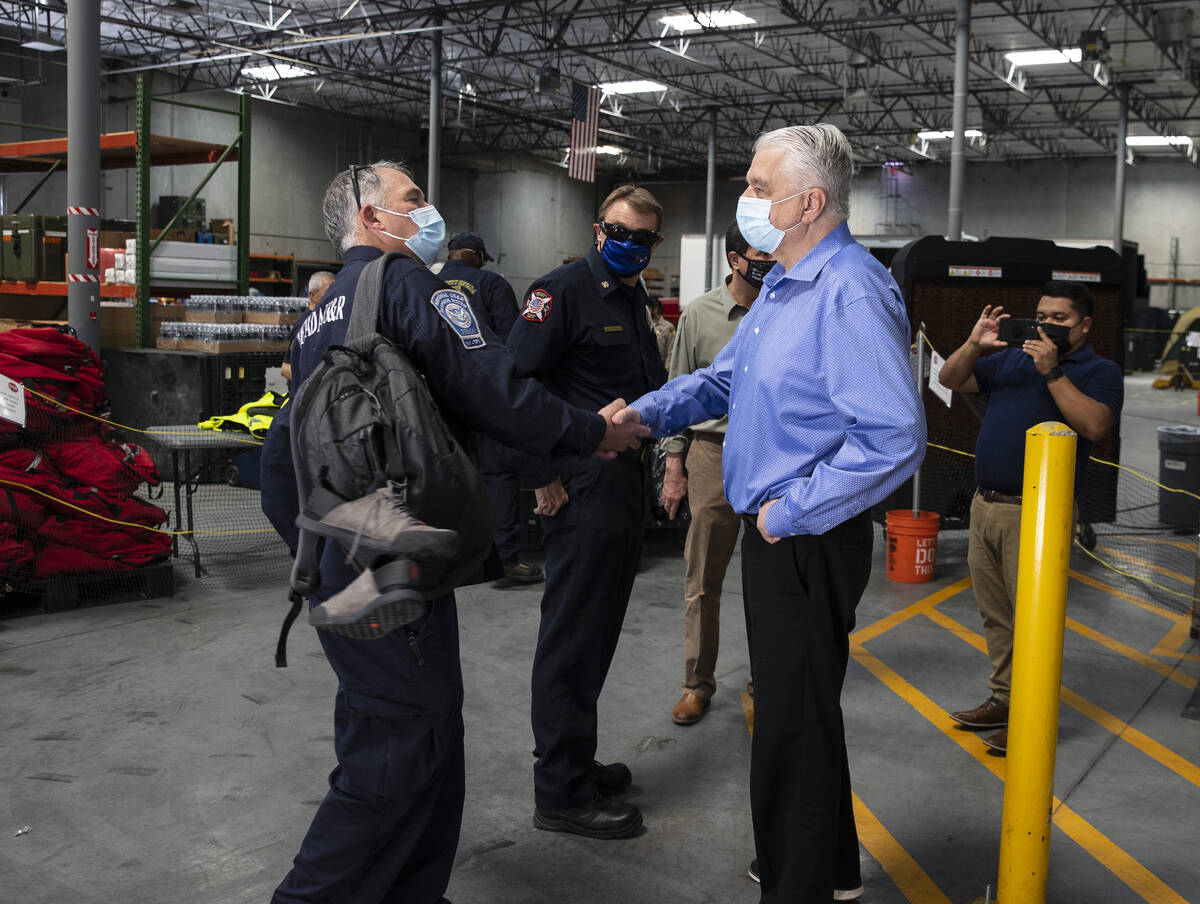 Gov. Steve Sisolak shakes hands with a members of the Nevada Task Force 1, Michael Porter, afte ...