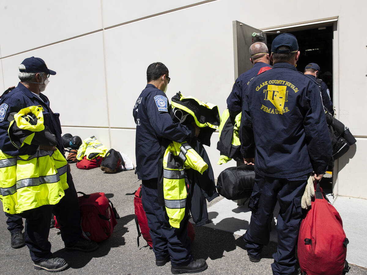 Members of the Nevada Task Force 1, including Dennis West, left, lined up, to return their equi ...