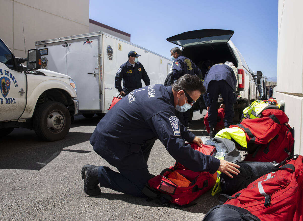 Members of the Nevada Task Force 1, including Tim Gardner, front, unload their equipments after ...