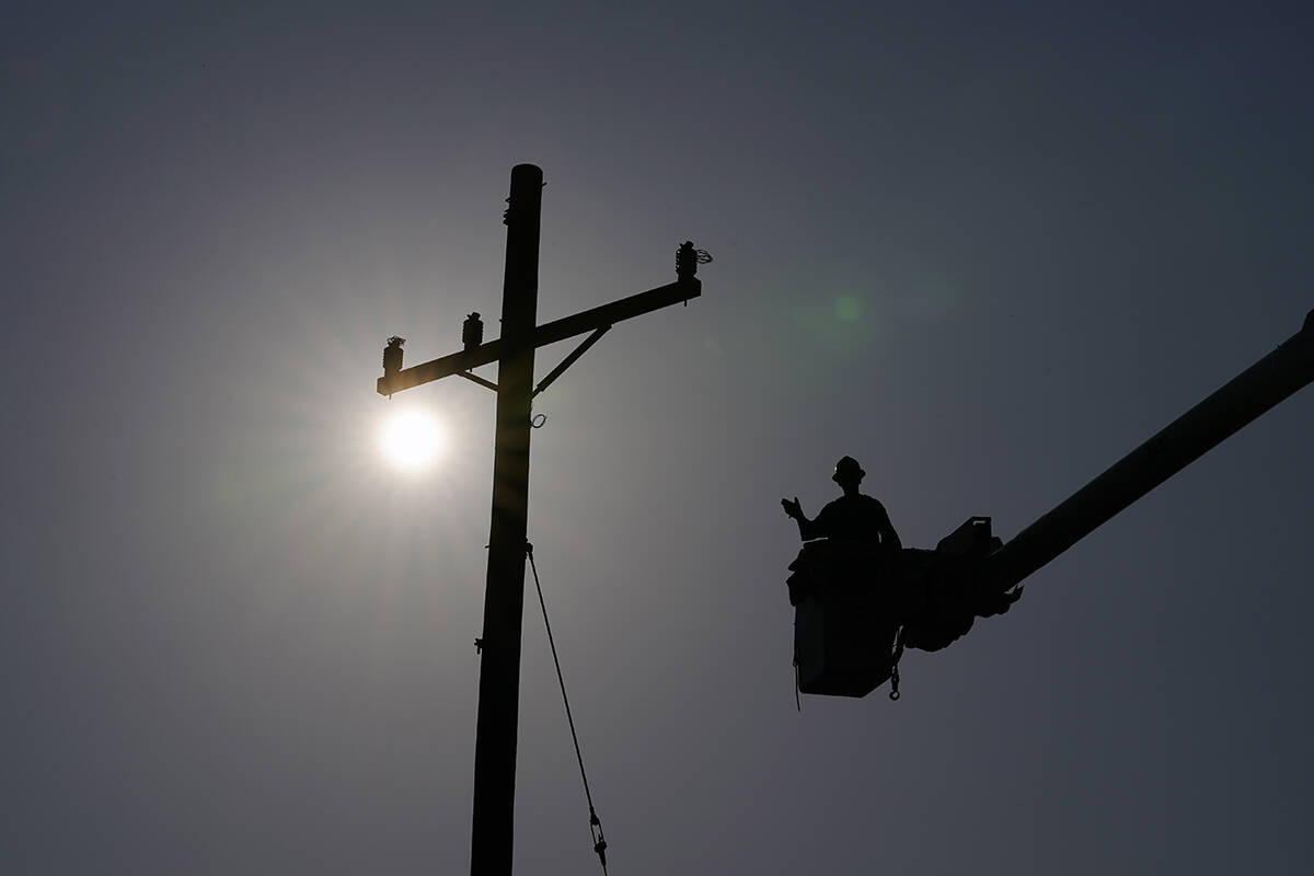In the aftermath of Hurricane Ida, a lineman gestures as he works on a power pole, Sunday, Sept ...