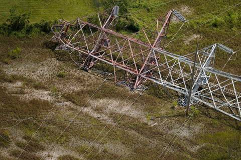 A twisted tower that carried crucial electrical feeder lines to the New Orleans metro area lies ...