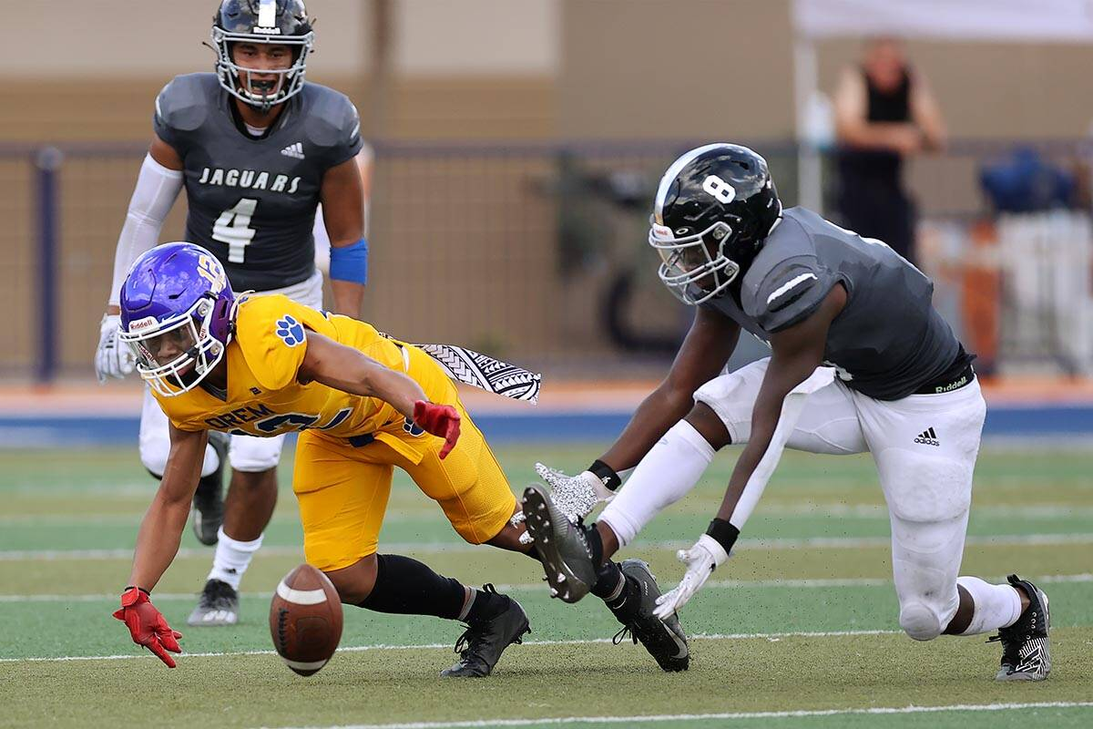 Orem's Tyson Ngaya (12) and Desert Pines' Labarrio Mays (8), dive short of the ball in the seco ...