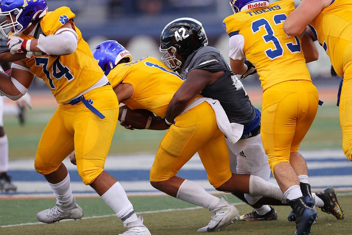Orem's Chase Tuatagaloa (1) is sacked by Desert Pines' Idgerinn Dean (42) in the second quarter ...
