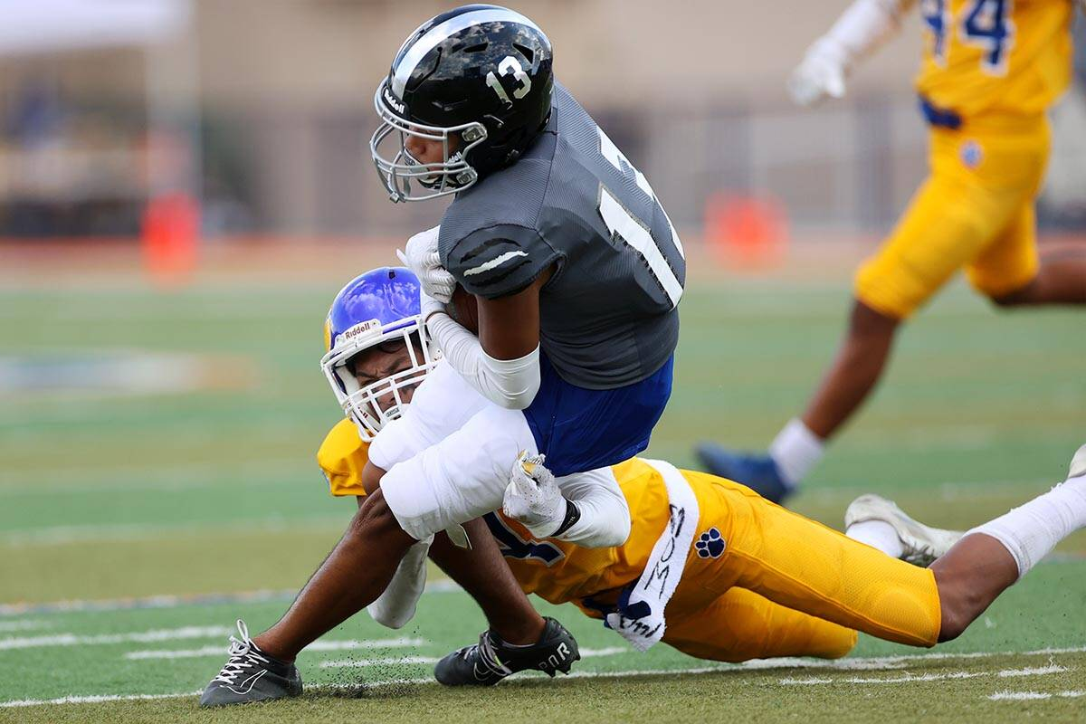 Desert Pines' Izley Manutai (13) is tackled by Orem's Shaun Niu jr. (4) after a catch in the se ...