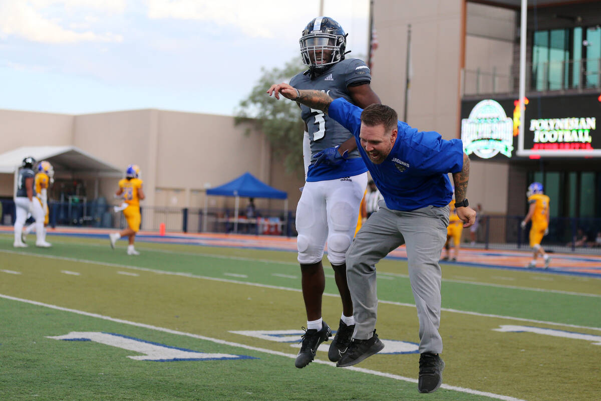 Desert Pines' Izley Manutai (13) celebrates a touchdown with a member of the coaching staff in ...