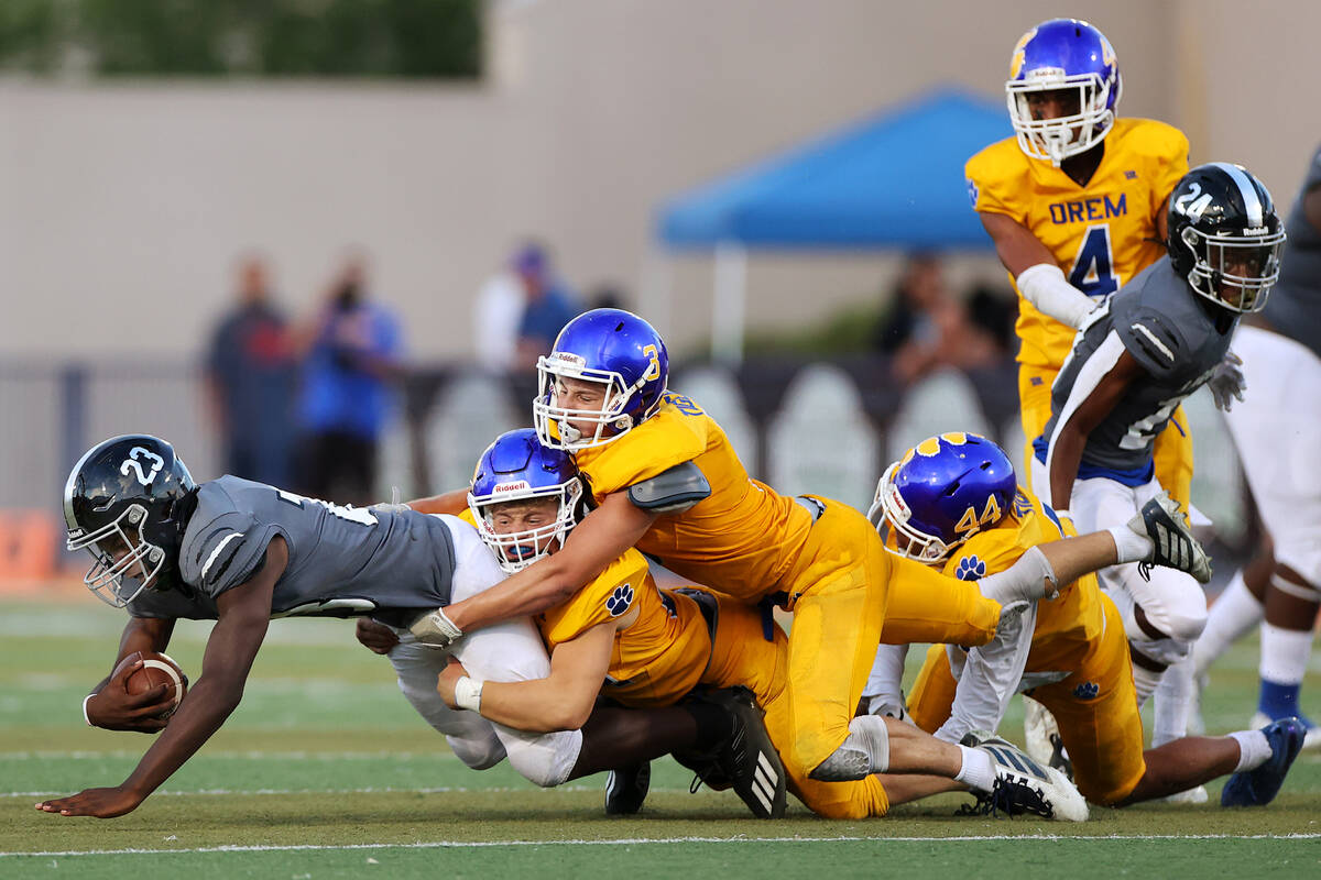 Desert Pines' Greg Burrell (23) is tackled by Orem's Tim Toa (44), Matthew Schroeder (24) and K ...