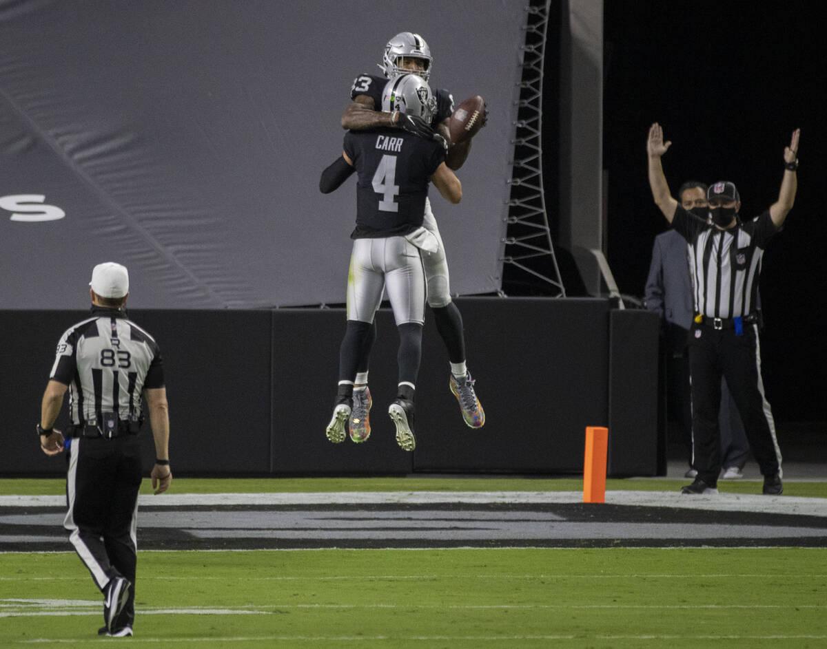 Las Vegas Raiders quarterback Derek Carr (4) celebrates with Las Vegas Raiders tight end Darren ...