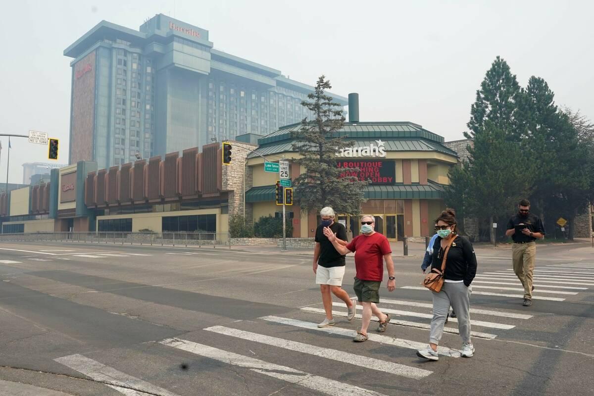 Harrah's Lake Tahoe Casino is shrouded in smoke as face mask wearing pedestrians cross the stre ...