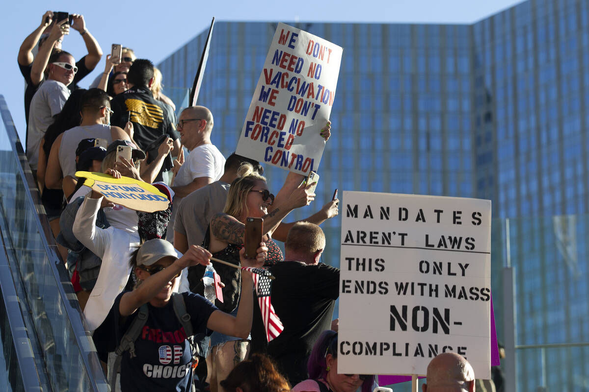 Demonstrators ride an escalator outside Planet Hollywood during an anti-mask, anti-vaccination ...