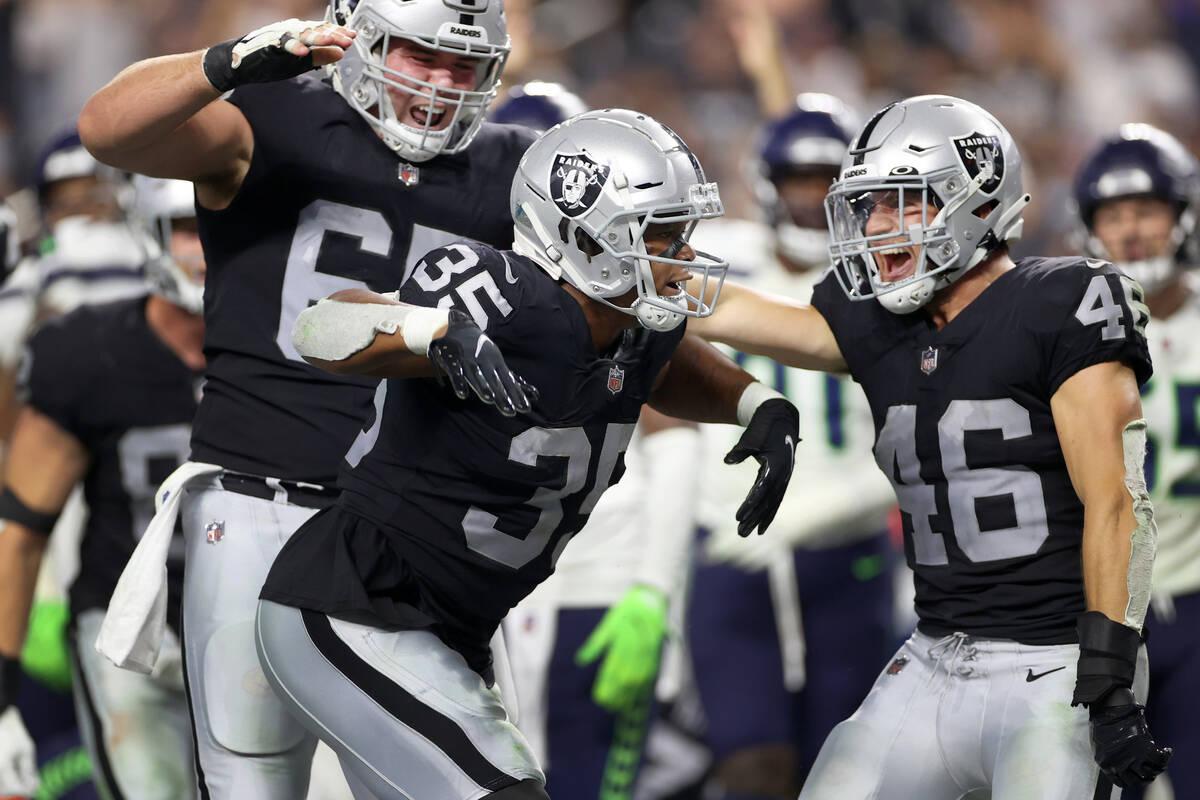 Las Vegas Raiders running back B.J. Emmons (35) celebrates a rushing touchdown, with center Jim ...