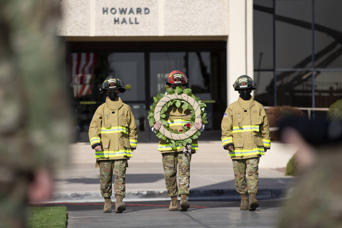 Firefighters participate in a wreath-hanging ceremony at the Nellis Fire and Emergency Services ...