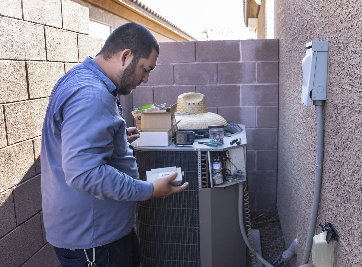 Windy City Air's technician Thomas Padron prepares to install a soft starter as he repairs an a ...