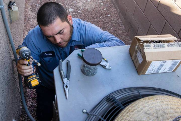 Windy City Air's technician Thomas Padron repairs an air conditioner at Vulcan St, on Friday, S ...