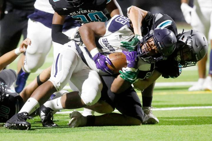 Shadow Ridge High School's Jaquieze Holland (25) is tackled by Silverado High School's Jaden Th ...