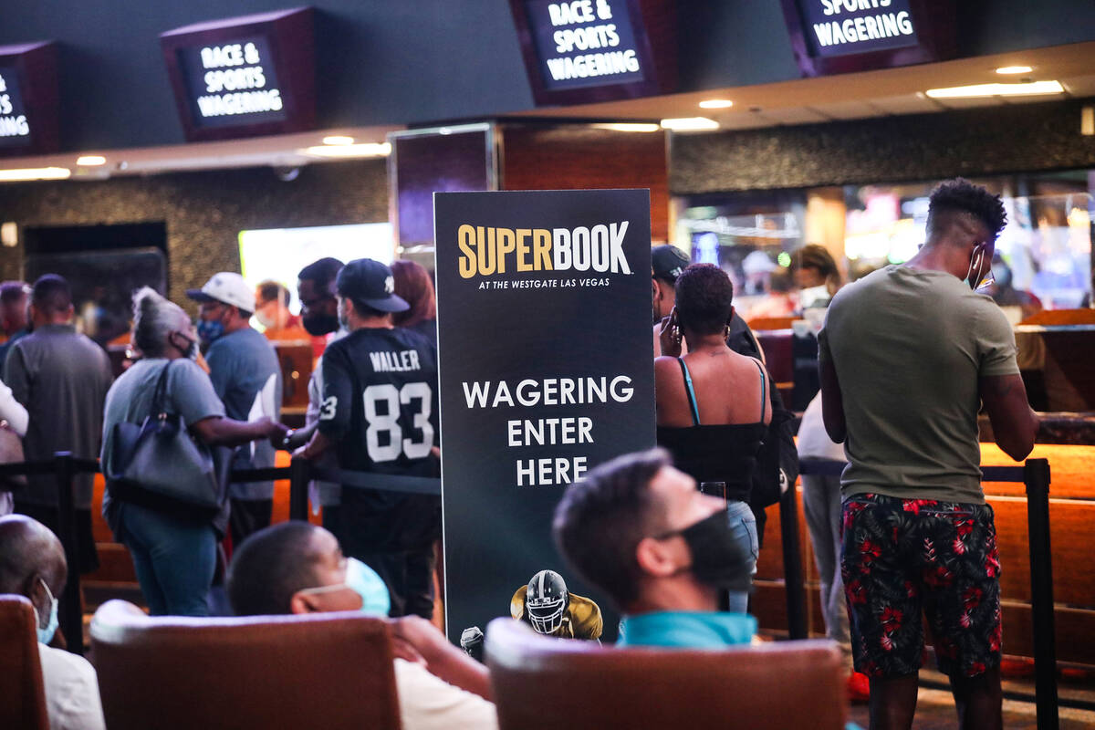 Guests wait in line to place their bets at the Sports Book at Westgate in Las Vegas, Sunday, Se ...