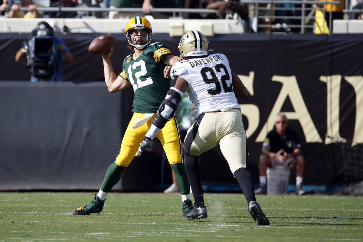 Green Bay Packers quarterback Aaron Rodgers (12) throws a pass as he is pressured by New Orlean ...