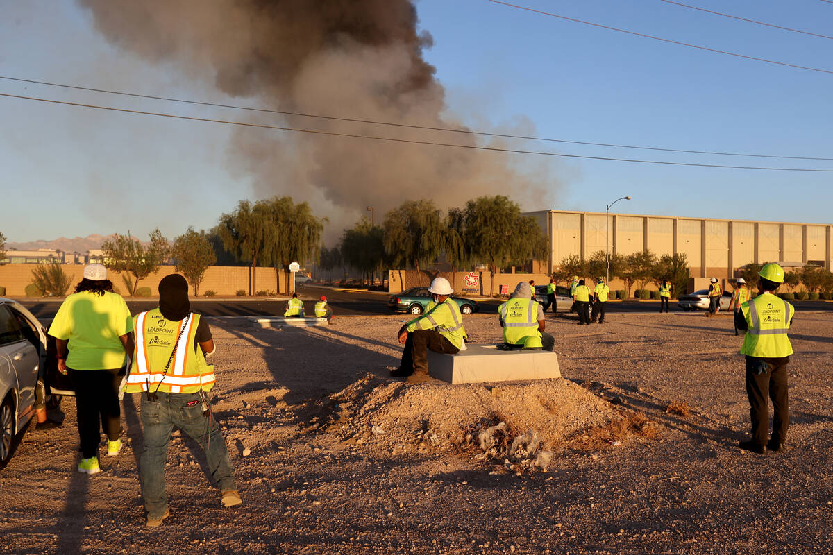 Workers wait as the North Las Vegas Fire Department battles a fire at a Republic Services recyc ...