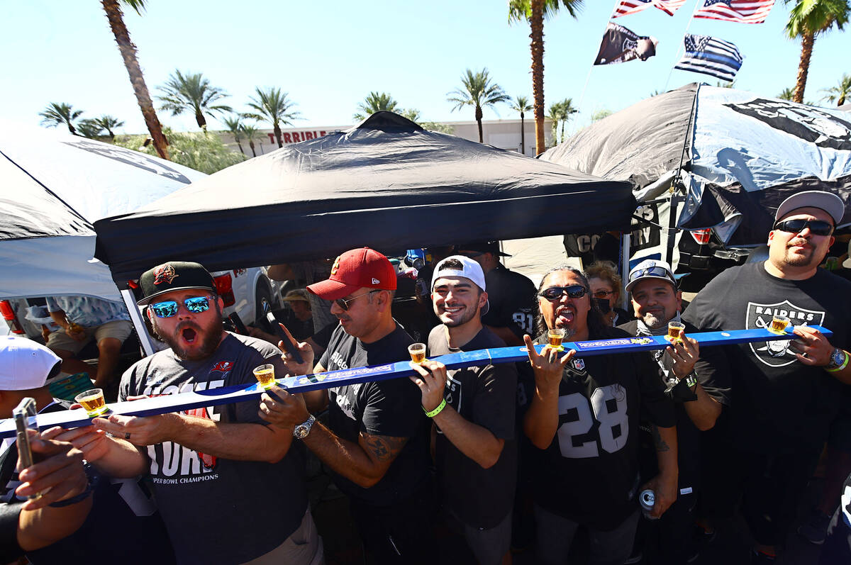 Fans are ready to drink while tailgating before an NFL football game between the Raiders and th ...