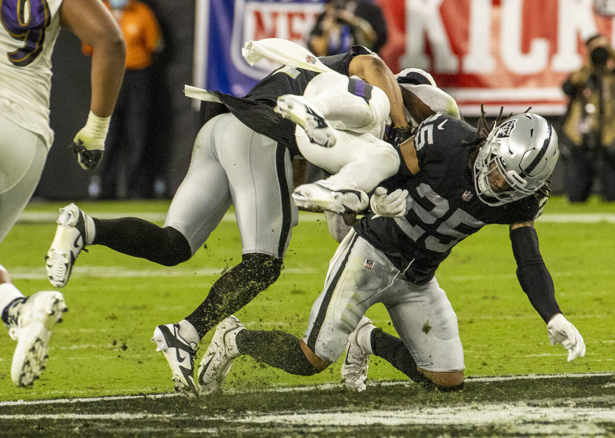 Baltimore Ravens running back Ty'Son Williams (34) upended by Raiders safety Trevon Moehrig (25 ...
