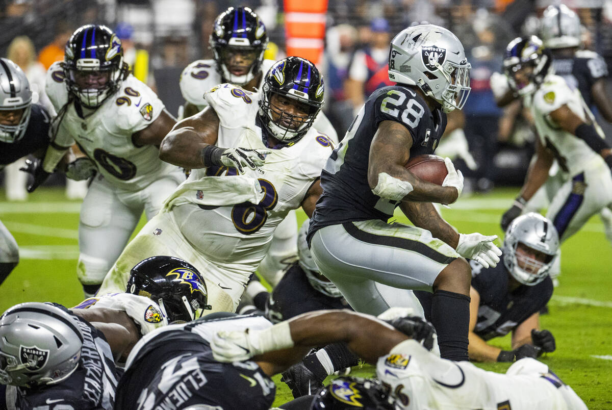 Raiders running back Josh Jacobs (28) heads towards the goal line as Baltimore Ravens defensive ...