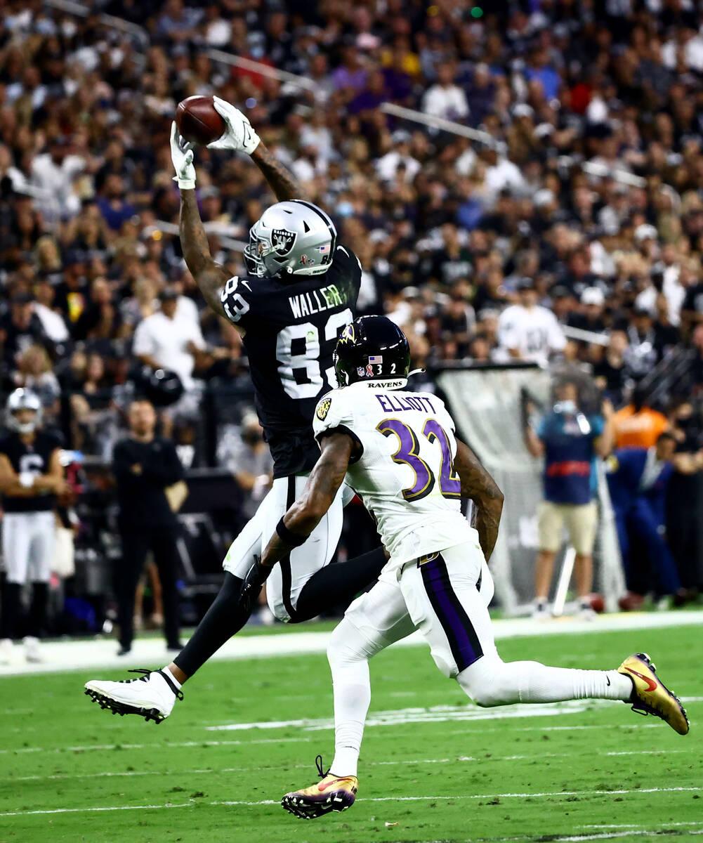 Raiders tight end Darren Waller (83) catches a pass as Baltimore Ravens defensive back DeShon E ...
