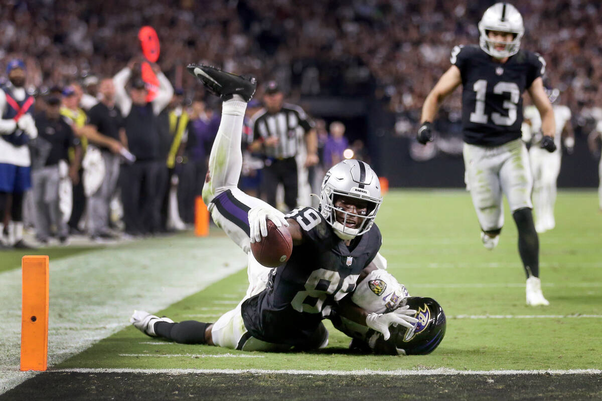 Raiders wide receiver Bryan Edwards (89) reaches short of a touchdown while getting tackled by ...