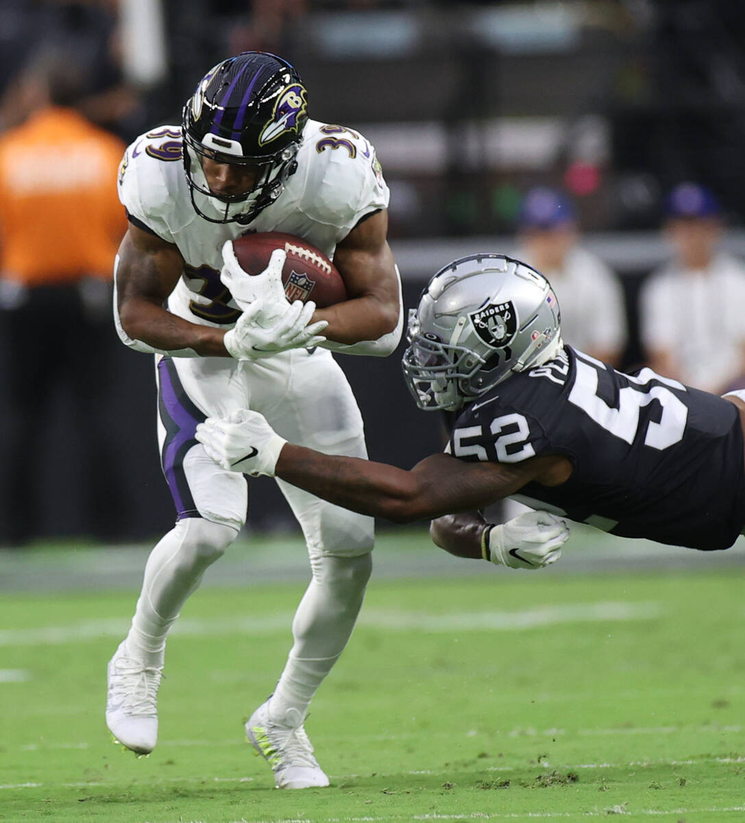 Baltimore Ravens running back Trenton Cannon (39) keeps a ball away from Raiders linebacker Den ...